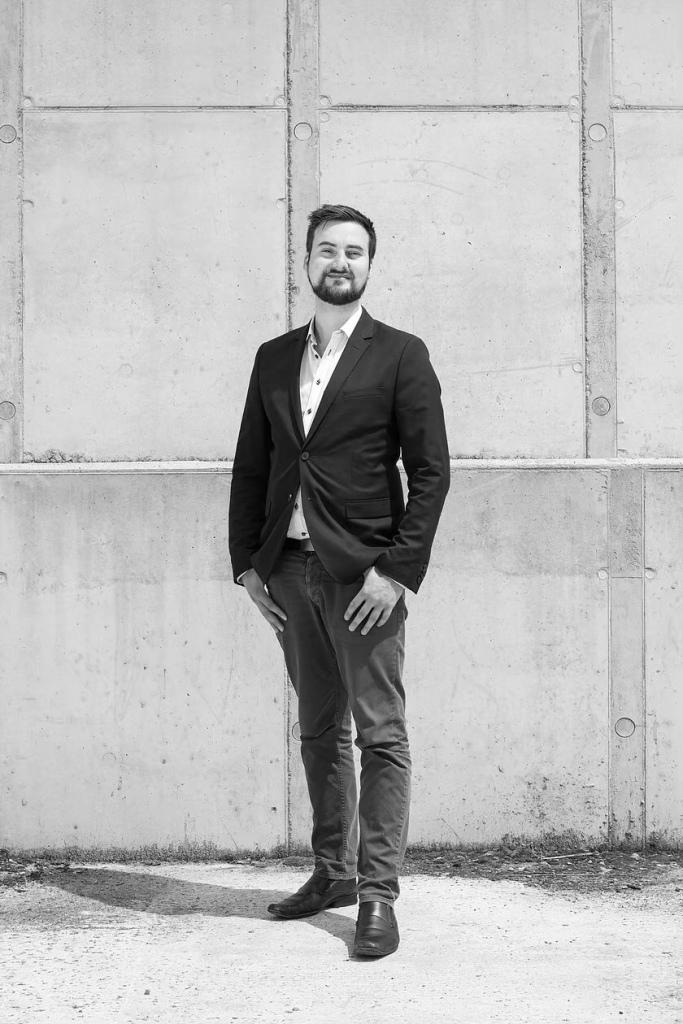 Schwarzweiß Foto von Herr in Business Style vor Beton Wand
